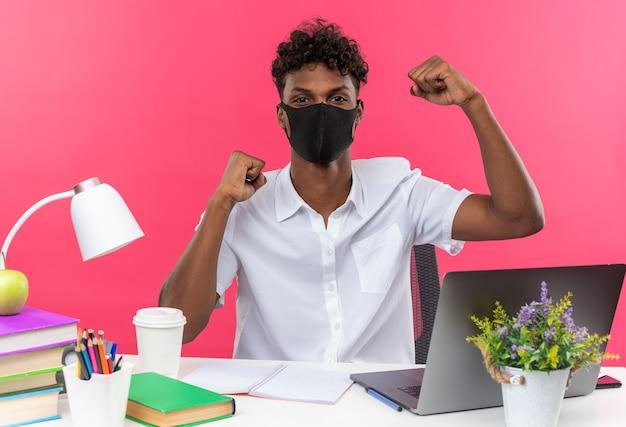 Pewny siebie młody afroamerykański uczeń noszący maskę siedzącą przy biurku z szkolnymi narzędziami podnoszącymi pięści w górę odizolowanych na różowej ścianie