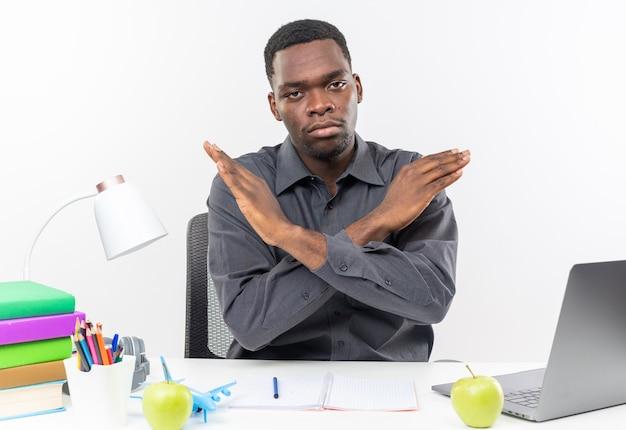 Pewny siebie młody afroamerykański uczeń siedzący przy biurku ze szkolnymi narzędziami krzyżującymi ręce i wskazujący na brak znaku
