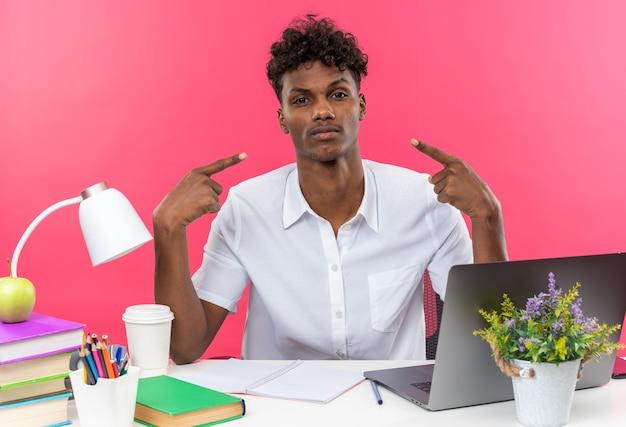 Pewny siebie młody afroamerykański uczeń siedzący przy biurku ze szkolnymi narzędziami wskazującymi na siebie