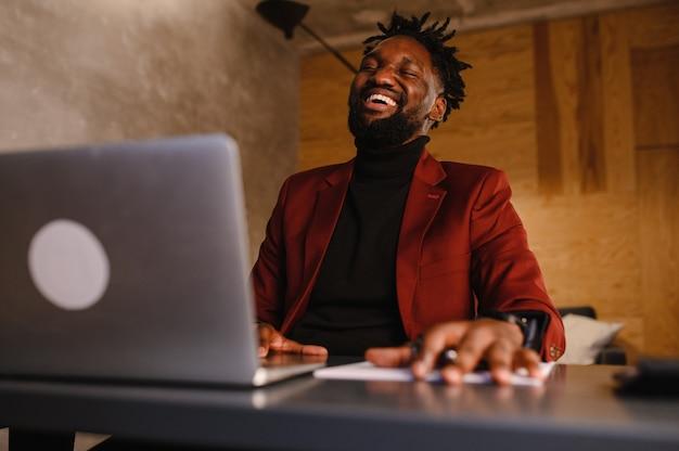 Pewny siebie młody afrykański mężczyzna patrzy na wideokonferencję z kamerą internetową w biurze szczęśliwy przedsiębiorca rasy mieszanej rozmawia rozmowa o pracy na czacie wideo online siedzieć przy biurku