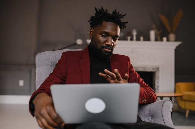 Pewny siebie młody afrykański mężczyzna patrzy na wideokonferencję z kamerą internetową w biurze