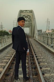 Pewny siebie młody azjata w garniturze, stojący na środku toru kolejowego, patrząc wstecz