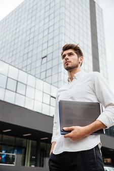 Pewny siebie młody biznesmen trzymający folder z dokumentami stojący w pobliżu centrum biznesowego