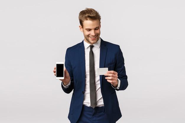 Pewny siebie młody blond biznesmen w niebieskim klasycznym garniturze, trzymając smartfon i kartę kredytową, pokazując mobilny wyświetlacz, metodę płatności online, aplikację finansową, stojąc na białym tle