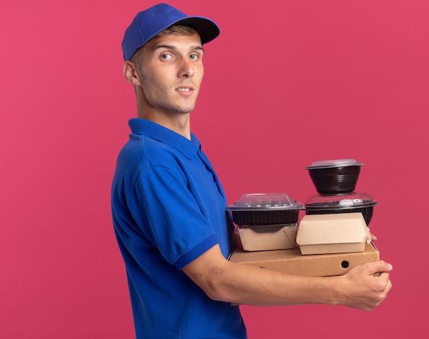 Pewny siebie młody blond chłopiec dostawy stoi bokiem, trzymając pojemniki z żywnością i paczki na pudełkach po pizzy odizolowane na różowej ścianie z miejscem na kopię