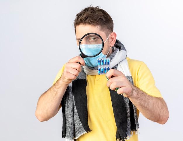 Pewny siebie młody blond chory słowiański mężczyzna w masce medycznej i szaliku patrzy na paczki pigułek medycznych przez szkło powiększające na białej ścianie z miejscem na kopię