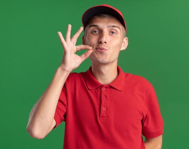 Pewny siebie młody blond kurier udaje, że zapina usta na zielono