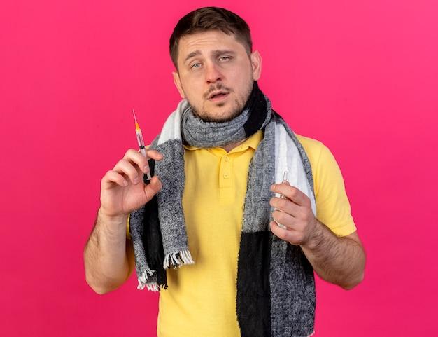 Pewny siebie młody blondyn chory sobie szalik trzyma strzykawkę i ampułkę na białym tle na różowej ścianie