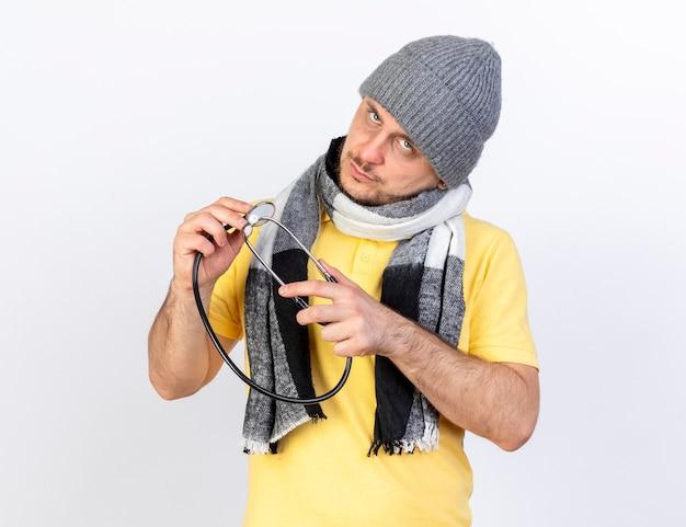 Pewny siebie młody blondyn chory w czapce zimowej i szaliku trzyma stetoskop i patrzy na przód na białym tle na białej ścianie