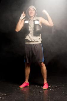 Pewny siebie młody bokser gestykulujący palcem pokazujący swój optymizm i wiarę, że może wygrać nadchodzącą walkę