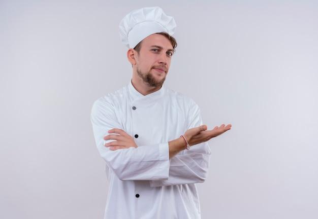 Pewny siebie młody brodaty szef kuchni ubrany w biały mundur kuchenki i kapelusz, podnosząc rękę i trzymając ręce złożone, patrząc na białą ścianę