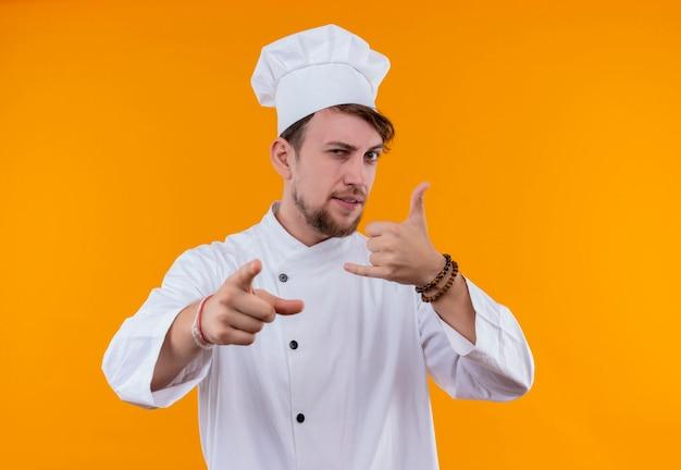 Pewny siebie młody brodaty szef kuchni w białym mundurze, pokazując gest do mnie ręką, patrząc na pomarańczową ścianę