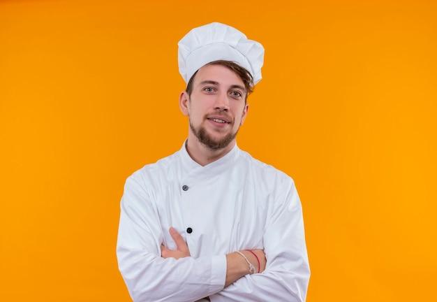 Pewny siebie młody brodaty szef kuchni w białym mundurze, trzymając ręce złożone, patrząc na pomarańczową ścianę