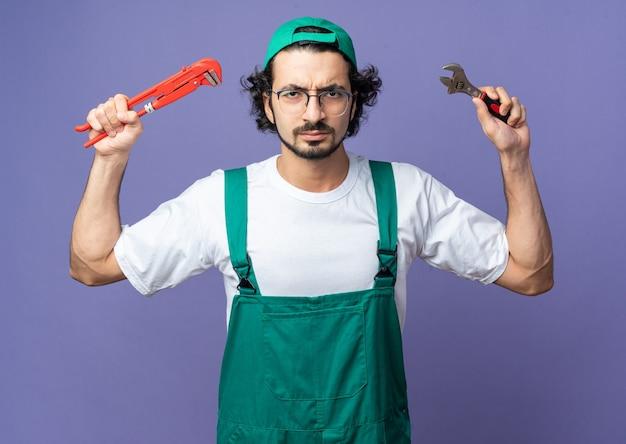Pewny siebie młody budowniczy mężczyzna ubrany w mundur z czapką, trzymający klucz płaski z kluczem