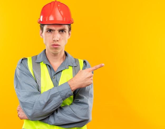 Pewny siebie młody budowniczy mężczyzna w jednolitych punktach z boku