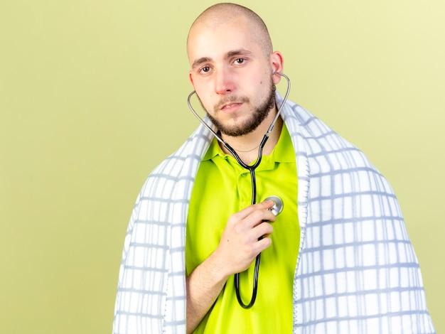 Pewny siebie młody chory zawinięty w kratę noszenie i trzymając stetoskop na białym tle na oliwkowej ścianie