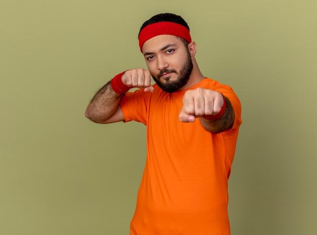 Pewny siebie młody człowiek sportowy noszenia opaski i opaski stojącej w pozie walki na białym tle na oliwkowym tle