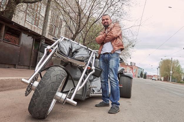 Pewny siebie młody człowiek stojący w pobliżu swojego motocykla na ulicy miasta