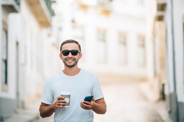 Pewny siebie młody człowiek w okularach trzymający filiżankę kawy i używający swojego smartfona podczas chodzenia na świeżym powietrzu
