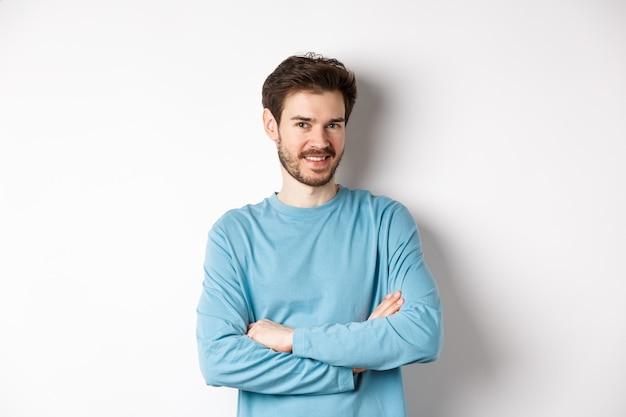 Pewny siebie młody człowiek z brodą, skrzyżowanymi rękami na piersi i uśmiech do kamery, stojąc jak profesjonalista na białym tle.