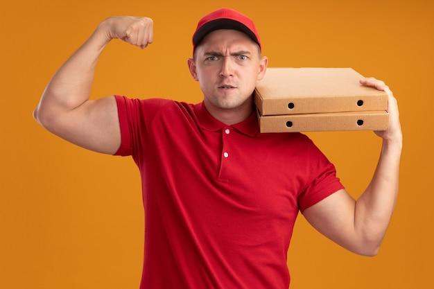 Pewny siebie młody dostawca ubrany w mundur z czapką, trzymając pudełka po pizzy na ramieniu, pokazując silny gest na pomarańczowej ścianie