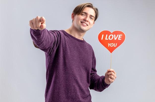 """Pewny siebie młody facet na walentynki trzymający czerwone serce na patyku z punktami tekstowymi """"kocham cię"""" w aparacie na białym tle"""
