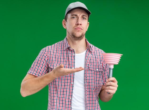 Pewny siebie, młody facet, sprzątacz, noszący czapkę trzymającą i wskazujący na tłok na białym tle na zielonym tle