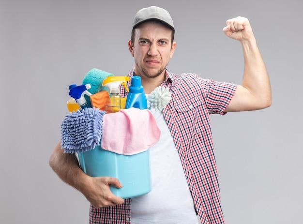 Pewny siebie, młody facet sprzątacz w czapce trzymającej wiadro z narzędziami do czyszczenia pokazujący silny gest na białym tle