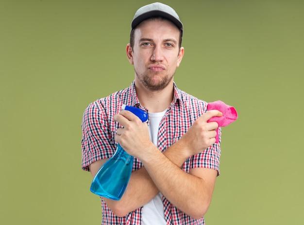 Pewny siebie młody facet sprzątający w czapce trzymającej i przekraczającej środek czyszczący ze szmatą odizolowaną na oliwkowozielonym tle