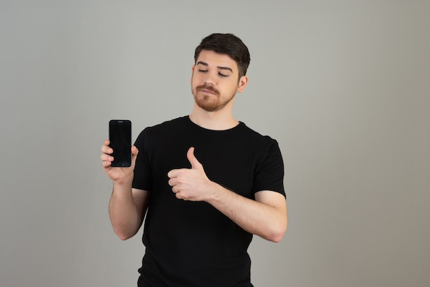 Pewny siebie młody facet trzymający telefon i wskazujący na szarość kciuki w górę.