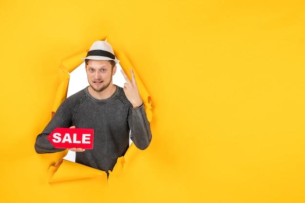 Pewny siebie młody facet trzymający znak sprzedaży i wykonujący gest zwycięstwa w rozdartej na żółtej ścianie
