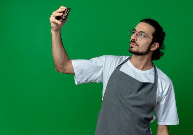 Pewny siebie młody fryzjer kaukaski mężczyzna w mundurze i okularach, biorąc selfie na białym tle na zielonym tle z miejsca na kopię