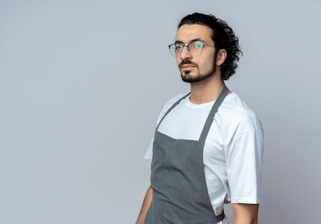 Pewny siebie młody kaukaski fryzjer męski w okularach i falującej opasce do włosów w mundurze stojącym w widoku profilu patrząc na kamerę na białym tle z miejsca na kopię