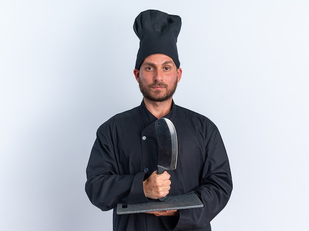 Pewny siebie młody kaukaski mężczyzna kucharz w mundurze szefa kuchni i czapce trzymającej deskę do krojenia i tasak na nim patrząc na kamerę na białym tle na białej ścianie