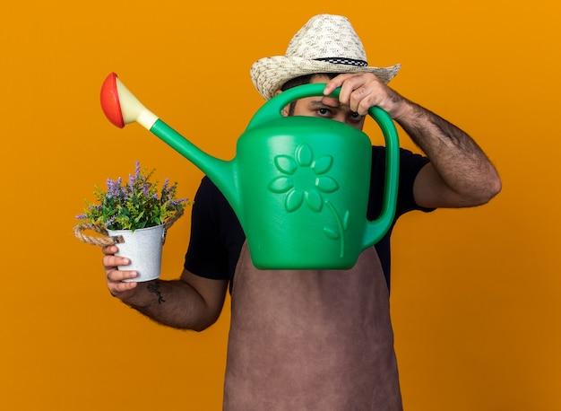 Pewny siebie młody kaukaski mężczyzna ogrodnik w kapeluszu ogrodniczym trzymającym doniczkę i patrzącym przez konewkę odizolowaną na pomarańczowej ścianie z kopią przestrzeni