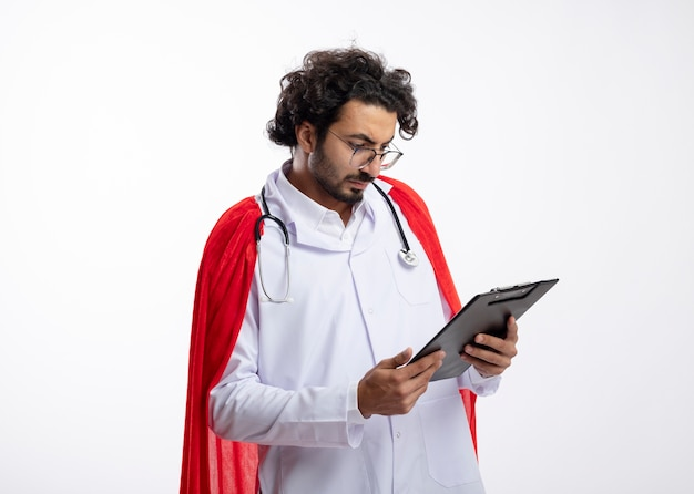 Pewny siebie młody kaukaski mężczyzna superbohatera w okularach optycznych w mundurze lekarza z czerwonym płaszczem i stetoskopem na szyi trzyma i patrzy na schowek na białej ścianie