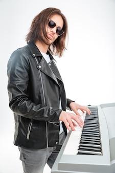 Pewny siebie młody klawiszowiec w okularach przeciwsłonecznych, stojący i grający na syntezatorze na białym tle