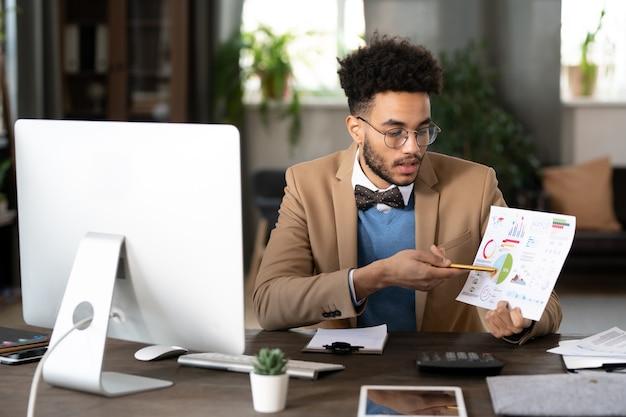 Pewny siebie młody konsultant finansowy w okularach siedzi przy stole i prezentuje wykresy klientowi za pośrednictwem aplikacji do wideokonferencji na komputerze