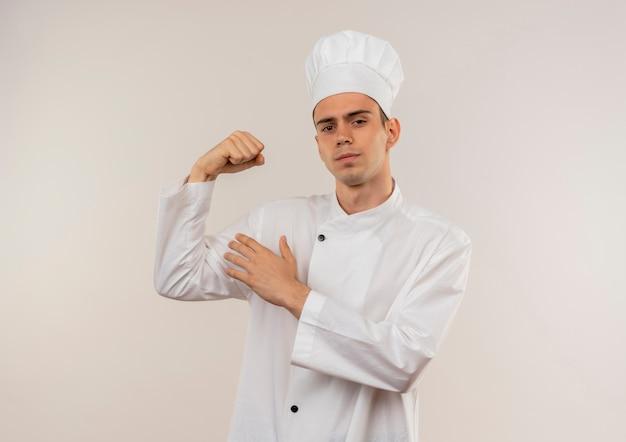 Pewny siebie młody kucharz mężczyzna ubrany w mundur szefa kuchni robi silny gest na odosobnionej białej ścianie z miejsca na kopię