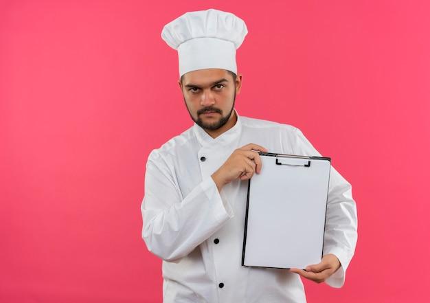 Pewny siebie młody kucharz w mundurze szefa kuchni pokazujący schowek na różowej ścianie z miejscem na kopię
