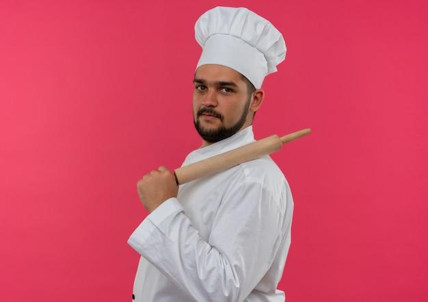 Pewny siebie młody kucharz w mundurze szefa kuchni stojący w widoku profilu, kładący wałek na ramieniu na różowej ścianie z miejscem na kopię