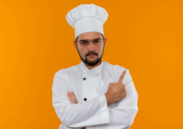 Pewny siebie młody kucharz w mundurze szefa kuchni stojący z zamkniętą postawą i wskazujący na bok odizolowany na pomarańczowej ścianie