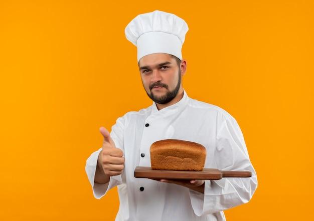 Pewny siebie młody kucharz w mundurze szefa kuchni trzymając deskę do krojenia z chlebem na nim pokazując kciuk na białym tle na pomarańczowej ścianie