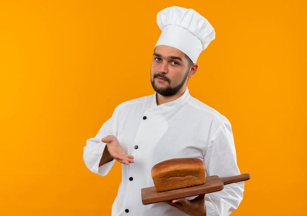 Pewny siebie młody kucharz w mundurze szefa kuchni trzymając i wskazując ręką na deskę do krojenia z chlebem na nim na białym tle na pomarańczowej ścianie