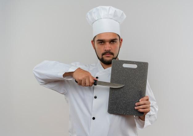 Pewny siebie młody kucharz w mundurze szefa kuchni trzymający deskę do krojenia i nóż na białym tle na białej ścianie