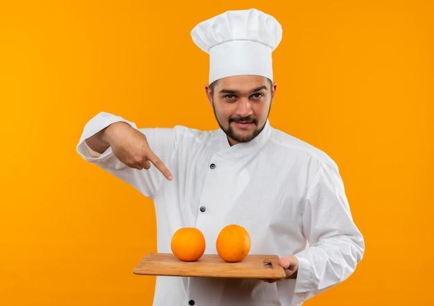 Pewny siebie młody kucharz w mundurze szefa kuchni trzymający deskę do krojenia i wskazujący na deskę do krojenia z pomarańczami na białym tle na pomarańczowej ścianie