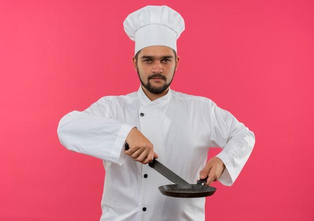 Pewny siebie młody kucharz w mundurze szefa kuchni trzymający nóż i patelnię na białym tle na różowej ścianie