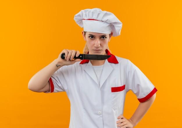 Pewny siebie młody ładny kucharz w mundurze szefa kuchni trzymający nóż z ręką w talii na białym tle na pomarańczowej ścianie