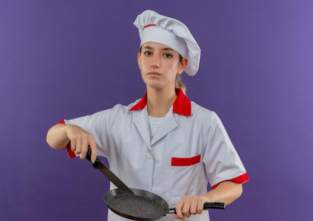 Pewny siebie młody ładny kucharz w mundurze szefa kuchni trzymający patelnię i nóż odizolowany na fioletowej ścianie