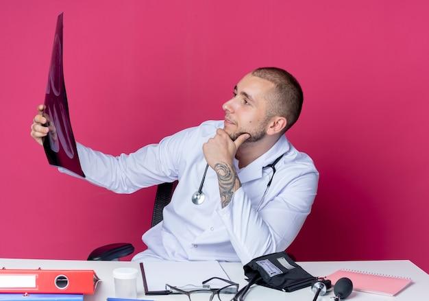 Pewny siebie młody lekarz płci męskiej ubrany w szlafrok medyczny i stetoskop siedzi przy biurku z narzędziami roboczymi, trzymając i patrząc na zdjęcie rentgenowskie z ręką na brodzie odizolowaną na różowo